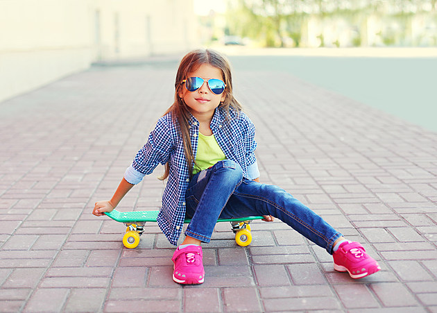 Fashion little girl child sitting on skateboard in city