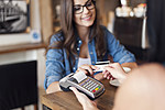 Smiling woman paying for coffee by credit card